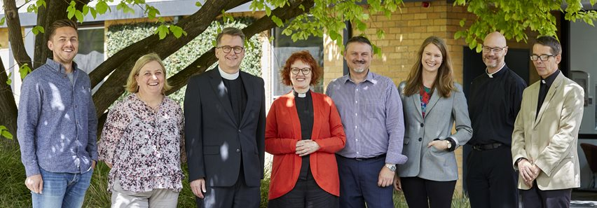 Image depicting three women, and two men who are staff members of Trinity College Theological School and standing in front of the Old Warden's Lodge.
