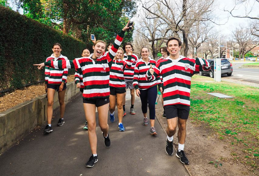 A group of Trinity students wearing their candystripe jumpers walking down the street and smiling.